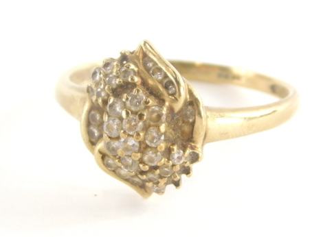 A 9ct gold dress ring, with central cross over floral detailing set with cz stones, in claw and tension settings, marked QVC, ring size T, 2.5g all in.