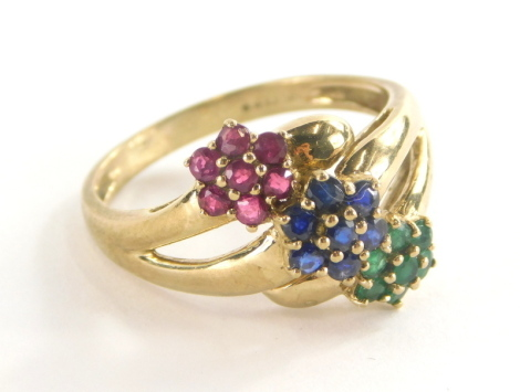 A 9ct gold dress ring, set with three layered design of flowers, with emeralds, rubies and sapphires, ring size S, 3.8g all in.