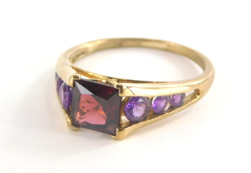 A 9ct gold dress ring, with square set red faceted stone and amethyst set tension shoulders, the band marked QVC, the central stone possibly garnet, ring size T, 3.3g all in.