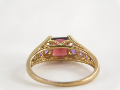 A 9ct gold dress ring, with square set red faceted stone and amethyst set tension shoulders, the band marked QVC, the central stone possibly garnet, ring size T, 3.3g all in. - 2