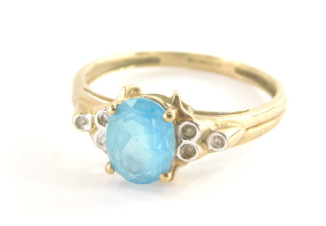 A 9ct gold dress ring, with pale blue oval topaz, in four claw setting, with stepped three stone cz shoulders, on a yellow metal band, marked QVC, ring size V, 2.6g all in.