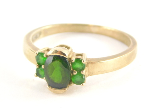 A 9ct gold dress ring, with central oval cut peridot, flanked by four peridots, each in claw setting, marked QVC, ring size S½, 2.6g all in.