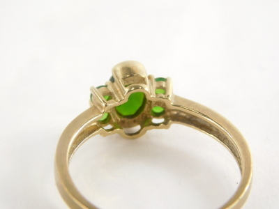 A 9ct gold dress ring, with central oval cut peridot, flanked by four peridots, each in claw setting, marked QVC, ring size S½, 2.6g all in. - 2