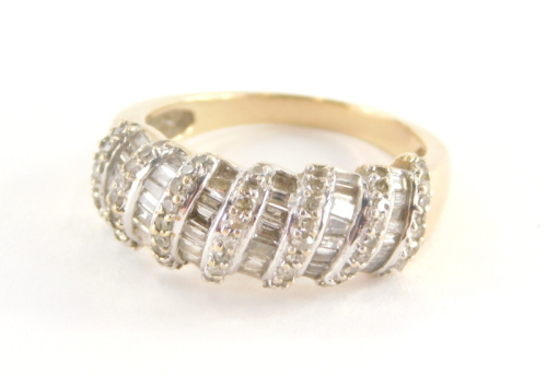 A diamond set dress ring, of half hoop design, with seven rows of round brilliant cut diamonds and six rows of baguette cut stones, in a white gold coloured setting on a yellow metal band, unmarked, believed to be 18ct gold, ring size O½, 5.1g all in.