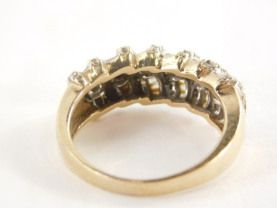 A diamond set dress ring, of half hoop design, with seven rows of round brilliant cut diamonds and six rows of baguette cut stones, in a white gold coloured setting on a yellow metal band, unmarked, believed to be 18ct gold, ring size O½, 5.1g all in. - 2