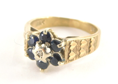 A 9ct gold cluster ring, with six sapphires and central illusions set tiny diamond and three layered heart shaped shoulders, ring size L½, 3g all in.