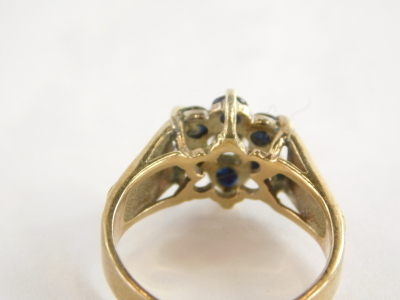 A 9ct gold cluster ring, with six sapphires and central illusions set tiny diamond and three layered heart shaped shoulders, ring size L½, 3g all in. - 2
