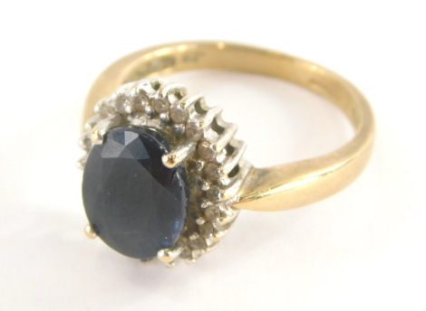 A 9ct gold sapphire and diamond dress ring, sapphire approx .25cts, the central oval cut sapphire surrounded by tiny diamonds, each in white gold setting on a yellow metal band, ring size P½, 4.6g all in.