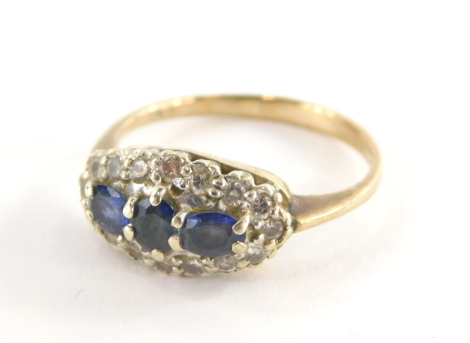 A 9ct gold sapphire and diamond dress ring, the oval ring head set with oval cut sapphires, in a white gold setting, with surround of round brilliant cut diamonds, on a yellow metal band, hallmarks rubbed, ring size S½, 3.5g all in.