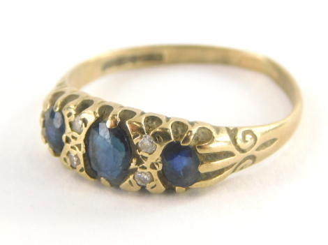 An 18ct gold sapphire and diamond gypsy ring, set with three oval cut sapphires and four tiny diamonds, on a misshapen band, ring size R, 2g all in.