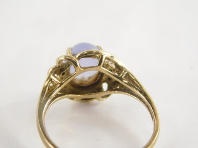 A 9ct gold dress ring, with central pale purple cabachon cut amethyst, and cz set shoulders and twist knot and pierced design splayed metal work, ring size R, 3.2g all in. - 2