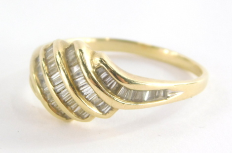 A diamond dress ring, with five layered twist design, each set with baguette cut diamonds, on a yellow metal band marked QVC 585, ring size T½, 4.1g all in.