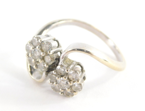 An 18ct white gold diamond twist ring, with two floral cluster diamond sections, on twist detailing, each diamond approx 0.10cts, in a claw setting, marked 750, ring size O½, 5.g all in.