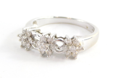 A 9ct white gold diamond dress ring, set with three diamond floral clusters and open work loop design, marked QVC, ring size O, 3.3g all in.