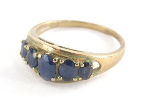 A dress ring, set with five oval cut dark blue faceted stones, pierced and oval setting on a yellow metal band stamped 9ct QVC, 3.3g all in. (AF)