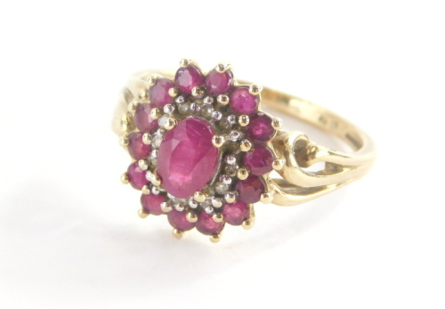 A 9ct gold cluster ring, with oval cut ruby in claw setting surrounded by cz stones and outer round brilliant cut rubies, on a two row twist design shoulders, ring size P½, marked QVC, 4.1g all in.