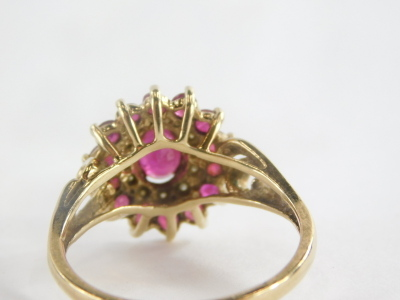 A 9ct gold cluster ring, with oval cut ruby in claw setting surrounded by cz stones and outer round brilliant cut rubies, on a two row twist design shoulders, ring size P½, marked QVC, 4.1g all in. - 2