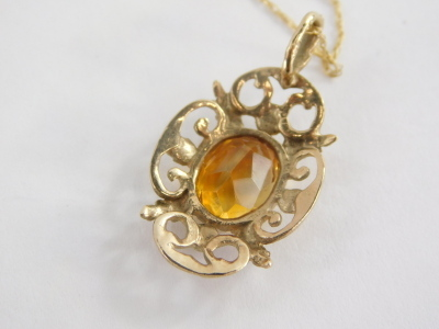 A 9ct gold pendant and chain, the floral pendant set with citrine, 3cm high, on a fine link chain, 46cm long, 2.3g all in. - 2