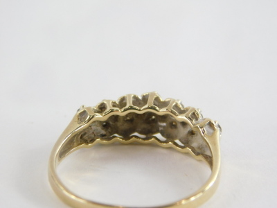 A 15ct gold dress ring, of half hoop design, set with tiny diamonds in claw setting with twist design backing, on a raised and pierced shank, 3.3g all in. - 2
