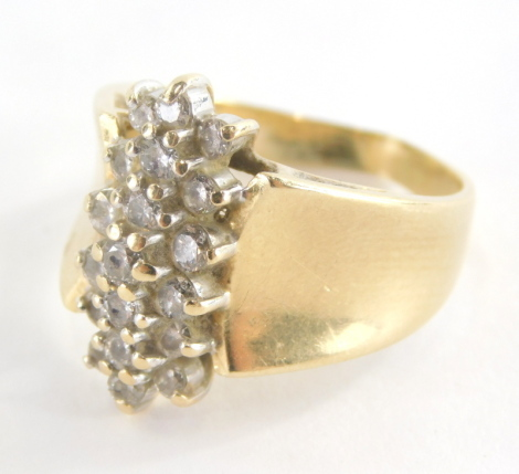 A diamond set dress ring, the central line design of round brilliant cut diamonds in claw setting forming three rows with dipped design shoulders, yellow metal stamped 14K ring size R, 8.3g all in.