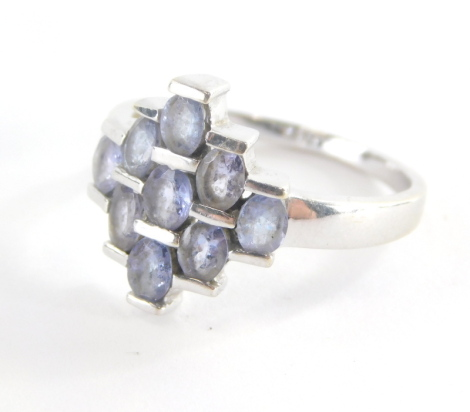 A dress ring, of layered design set with oval pale amethyst with three row central bar, and graduated outer layers, white metal, unmarked, ring size O, 3.6g all in.
