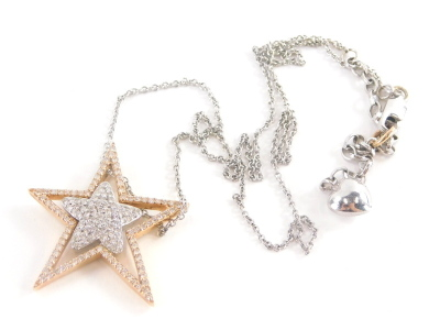A star pendant and chain, the star pendant set with tiny diamonds with five point rose gold outer star and five point white gold inner star, on a curb link chain, with heart drop marked 14kt, the pendant 3.5cm high, the chain 44cm long, 8.9g all in.