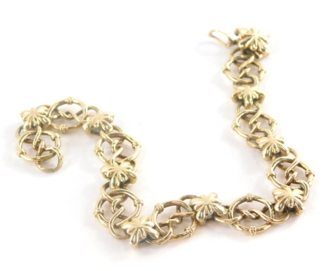 A 9ct gold bracelet, fancy link with elaborate loop and twist design with flower pendant brakes, and clasp to match, with safety clip, 22cm long, 23.3g.