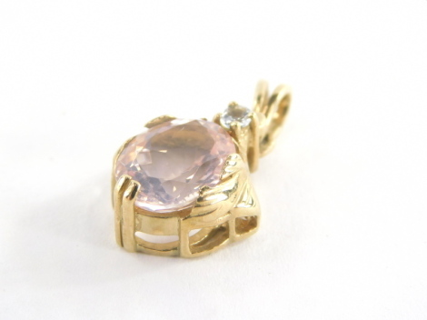 A 9ct gold pendant, with oval cut pink topaz and single cz stone, in a yellow metal mount with twin pendant loop, 2.5cm high, 2.4g all in.
