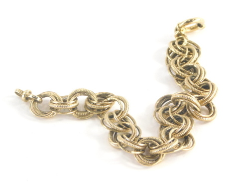 A 9ct gold multi link bracelet, each link comprising three loops, one with twist detailing, the two outer with plain design, on a circular loop clasp, 20.5cm long, 12.3g.