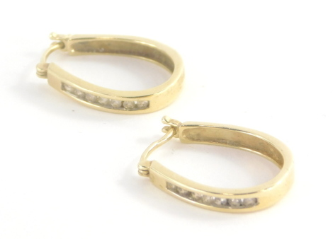 A pair of 9ct gold and diamond set hoop earrings, with seven tension set tiny diamonds to each hoop, 2cm high, 3.3g all in.