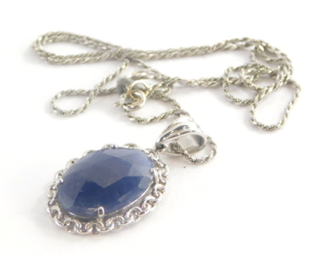 A sapphire pendant and chain, the oval flattened sapphire with chain border, with single pendant loop marked 375, 3.5cm high, on a fancy link white gold chain, 42cm long marked 750, 7.1g all in.