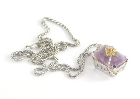 A topaz set pendant and chain, the rectangular cut pink topaz in a raised basket white gold setting, with an arched flower section set with tiny diamonds, white metal unmarked believed to be 18ct white gold, 3cm high on a fancy link chain 50cm long, stamp