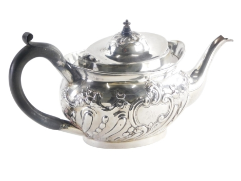 A late Victorian silver teapot, the body decorated with scrolls, fruit, leaves, with an initialled cartouche ECM, the base with the inscription 'Presented to The Rev E C Markie BA for 8 years curate of Bolton Percy by the parishioners as a token of their