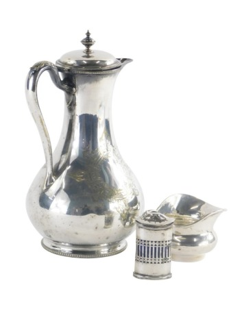 A late 19th/early 20thC helmet shaped silver cream jug, with a decorative handle, hallmarks rubbed, 2oz, and a George V silver pepper pot with a pierced body and blue glass liner, Chester 1927, 1oz, without liner, and a silver plated hot water jug. (3)