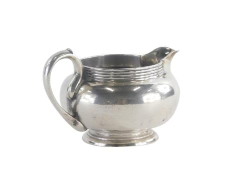 A George V silver milk jug, the top with a multiple line band border, on a pedestal base, London 1910, 6cm high, 6oz. (AF)