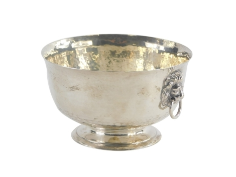 A George V silver two handled bowl, with hammered decoration, the two handles cast with lion heads, on a pedestal base, London 1914, 5¼oz, 6.5cm high, 11.5cm diameter.