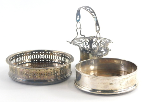 An Elizabeth II silver wine coaster, of plain form with turned wooden base, London 1990, a silver plated example with pierced decoration and a silver basket with pierced decoration. (AF, 3)