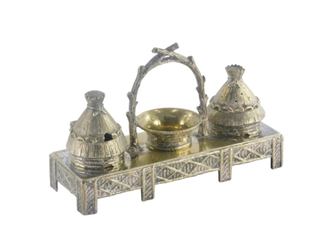 A late 19th/early 20thC novelty silver plated cruet stand, the condiment pot and pepper pot cast in the form of beehives, the central compartment formed in the shape of a two handled basket, on a rectangular stand, the base 10cm x 6cm.