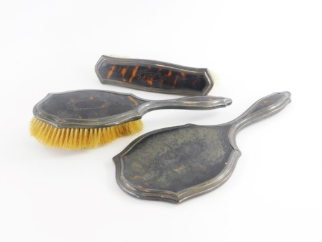 A George V tortoiseshell and silver mounted three piece dressing table set, comprising hand mirror, hairbrush and a clothes brush, Birmingham 1920 and 1923. (3)