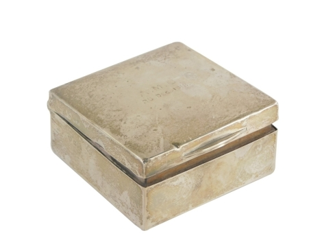 An early 20thC silver cigarette box, of square form, the top initialled AMC, 25th December 1912, the hinged lid revealing a treen interior, hallmarks rubbed, 8.5cm x 8.5cm x 4.5cm.