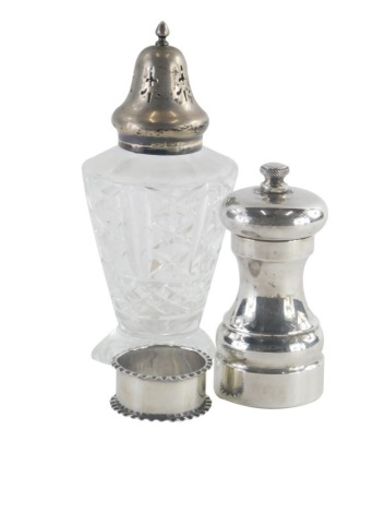 A 20thC silver pepper grinder, of plain form, marked 925 to base, a cut glass and silver topped sugar sifter, and a silver napkin ring. (3)