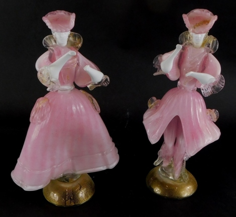 A pair of Murano Italian glass figurines, depicting a lady and gentleman each wearing pink costume, on a domed foot with gold inclusions, labelled to reverse Made In New Art 90 (1AF), 31cm high.