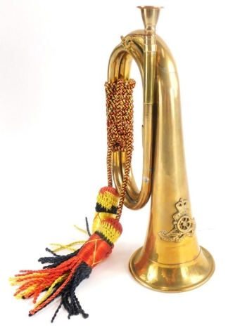 A Royal Artillery brass bugle, with rope tassels and Ubigue crest cast to front, 28cm long.Auctioneer Announce: This is an Indian made reproduction.