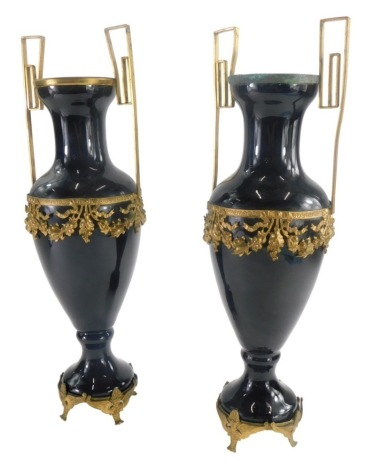 A pair of 19thC continental black glass two handled urns, with shaped brass handles, and a moulded brass band decorated with fruit, leaves and bows, on brass detachable feet, 39cm high. (2)