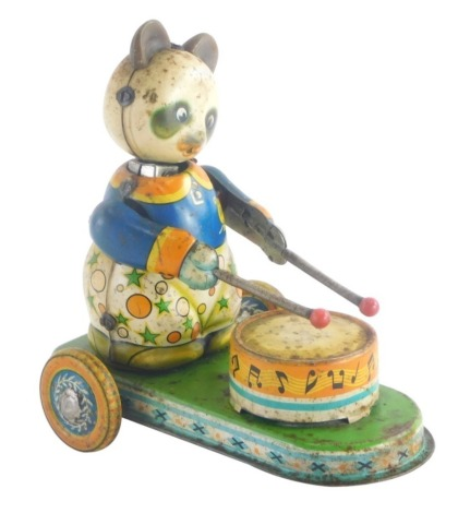 A mid 20thC tin plate wind up model toy of a panda playing a drum, 12cm high, 13cm wide.
