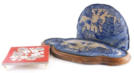 A 19thC beadwork panel, depicting an Oriental scene with bridge, boat, various houses, birds, in differing shades of blue, inset into a hardwood base, a similar teapot cosy, and a further bead work small table or tray, on four ivory acorn shaped feet. (3)