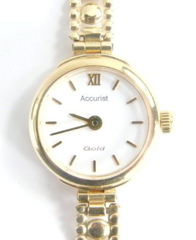 A 9ct gold Accurist ladies wristwatch, with white dial, on a pleated design 9ct gold bracelet in 9ct gold watch mount, 17cm long, 11.2g all in.