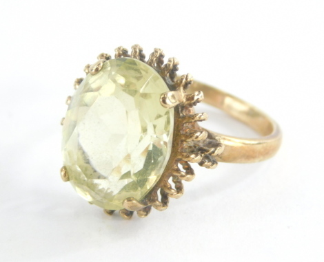 A 9ct gold dress ring, set with central pale green stone possibly peridot, in a splayed and arched raised shank in four claw setting, ring size R½, 5.9g all in.