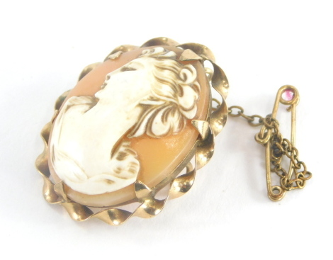 A 9ct gold framed shell cameo brooch, the oval shell raised cameo depicting figure of lady looking left, with waved design outer 9ct gold frame on safety chain, 2.5cm high, 6g all in.