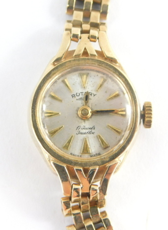 A Rotary 9ct gold ladies wristwatch, with small silver coloured circular dial, 1.2cm wide, on a three row 9ct gold bracelet, with safety chain, 14.1g all in, boxed.
